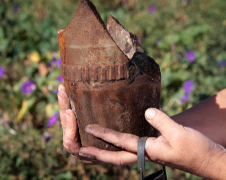 Female hands holds the remains of an artillery shell that destroyed her home after the bombing separatists in the village Krasny Liman Donetsk region, Ukraine