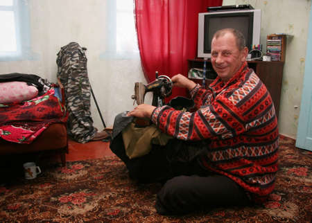 illustrative material: VOLYN, UKRAINE - 04 November 2008: Unknown man amputee sewing on floor in room at his home