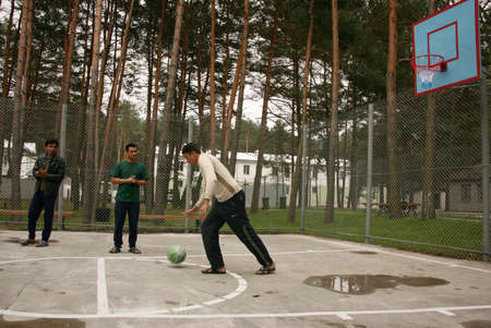 ZHURAVYCHI, UKRAINE - 12 September 2008: Men playing basketball in the temporary residence of foreigners and stateless persons who illegally stay in Ukraine