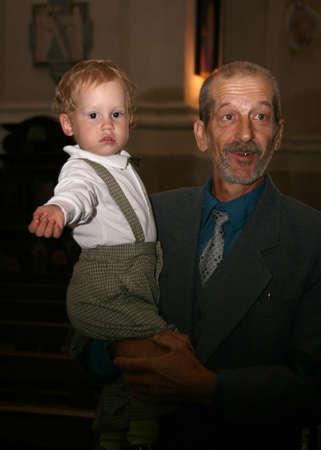 LUTSK, UKRAINE - 26 July 2009: Unknown grandfather holding grandson in church