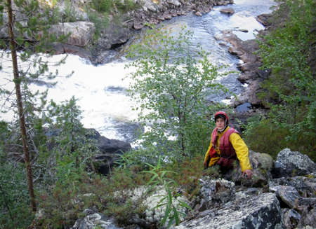 KOLSKYY, RUSSIA - 11 AUGUST 2008: Man in protective helmets and life jackets on the rock near river