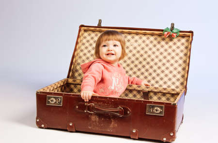 Little girl sits in a suitcase on light background Stock Photo