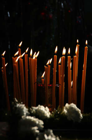 Candles burning and flowers in church. Shallow depth of field.