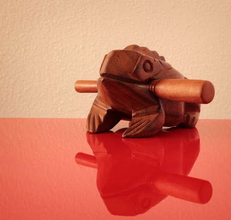 Wooden sculpture of frog on red mirror surface