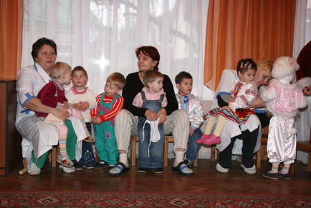 casualty: LUTSK, UKRAINE - 19 December 2008: Caregiver and little orphan children in an orphanage