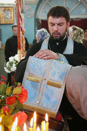 VOYUTYN, UKRAINE - 14 October 2008: Priest covered robe head of woman during confession in church