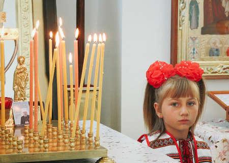 VOYUTYN, UKRAINE - 23 August 2015: Little ukrainian girl posing in Orthodox Church Editorial