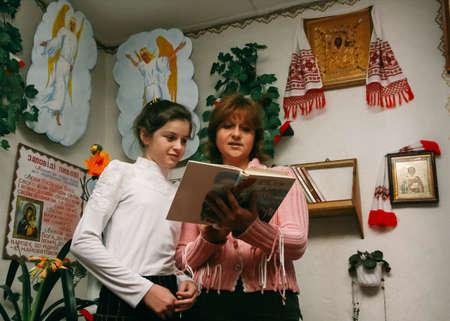 スタラ、ウクライナ - 2008 年 12 月 23 日: 女性および女の子の学校で聖書を読む 報道画像