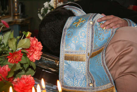 Priest covered robe head of woman during confession in church