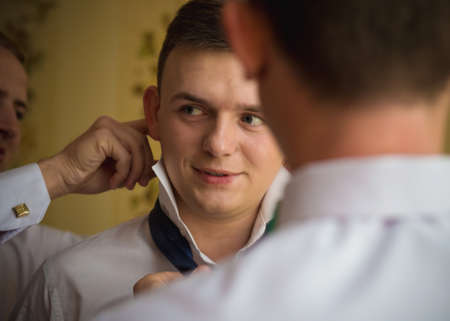 VILHIVKA, UKRAINE - 21 May 2017: Groomsman helps to wear a tie to the groom in room. Shallow depth of field. Editorial