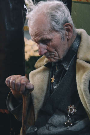 VOYUTYN, UKRAINE - 14 October 2008: The gray-haired 90-year-old man with military medals sitting at church Editorial