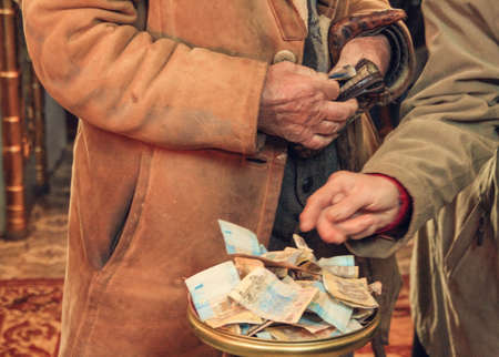 Hands of old man with a wallet at the plate to raise money in the Orthodox Church