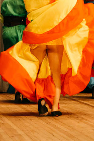 Young woman dancing in the studio and lifting up her colorful dress, showing her nice legs Foto de archivo