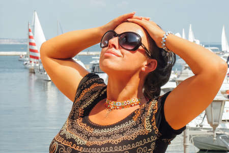 Caucasian brunette woman in marina against yachts in port