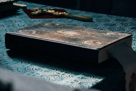 Orthodox Bible and cross. Shallow depth of field. Focus on the the central part of the Bible.