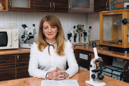 Caucasian woman with microscope at laboratory Stock Photo