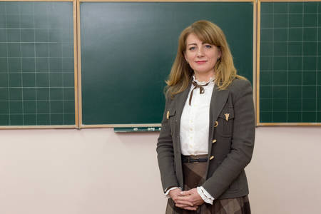 Stylish middle-aged woman teacher standing in front of the class blackboard looking thoughtfully at the camera with a smile