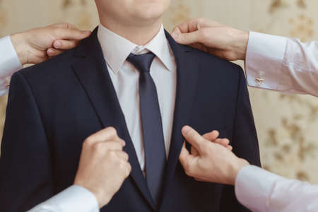 Groomsman helps to wear a jacket to the groom in room. Shallow depth of field. Stock Photo