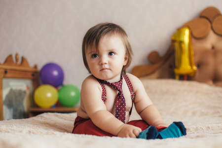 Little boy in tie and pants with suspenders. Shallow depth of field. Stock Photo