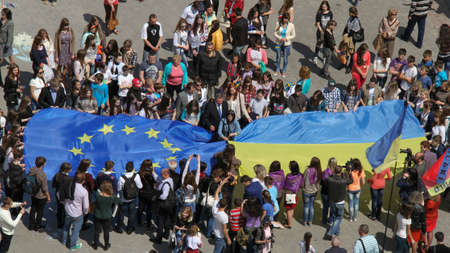 Lutsk, Volyn / Ukraine - May 17 2014: Young people holding a big flags of European Union and Ukraine during Europe Day Editoriali