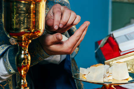 Hands of priest and orthodox prosphora for communion during holiday prayers in church. Shallow depth of field. Stock Photo