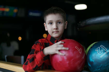 Little boy bowling with ball in alley