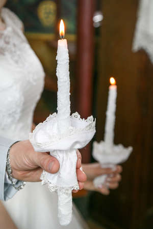 The groom and the bride hold candles in their hands
