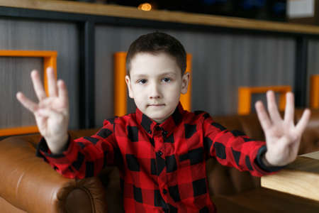 Little boy shows the number eight fingers. Shallow depth of field. 스톡 콘텐츠