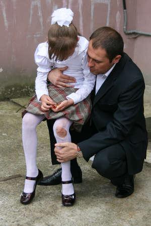 LUTSK, Volyn / UCRAINA - 30 agosto 2009: Lutsk, Volyn / Ucraina - 30 agosto 2009: Padre che abbraccia e calma la piccola figlia in collant a brandelli Editoriali