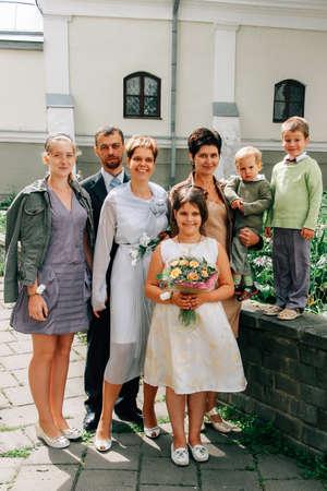 LUTSK, Volyn  UKRAINE - July 26 2009: Groom and bride with guests posing near church Sajtókép