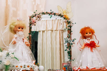 Two dolls in a dress of the bride on a wall background 免版税图像