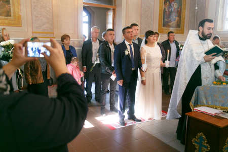 Lutsk, Volyn  Ukraine - September 30 2018: Woman making video with smartphone at Orthodox church during wedding ceremony