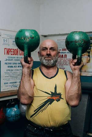 Novograd, Volyn  Ukraine - March 31 2009: Senior man working out using kettlebell in rural gym Editorial
