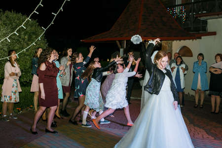 Cuman, Volyn  Ukraine - April 29 2018: Happy bride throwing bouquet and having fun at the wedding reception next to restaurant Sajtókép