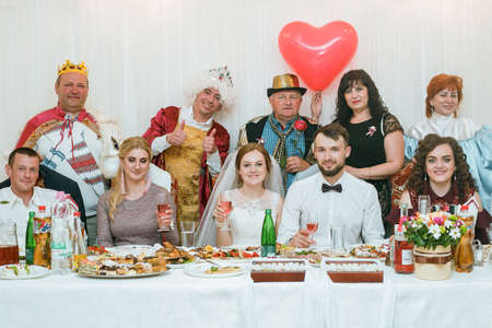 Cuman, Volyn  Ukraine - April 29 2018: Bride and groom with friends posing in a restaurant
