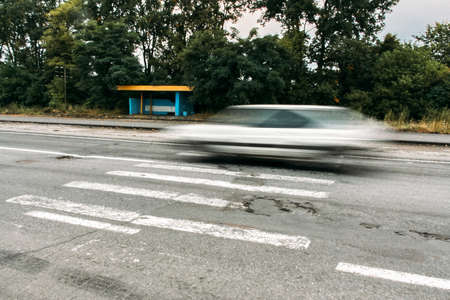 White car at high speed crosses a pedestrian crossing, a motion blur effect Banque d'images