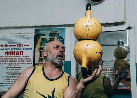 Novograd, Volyn  Ukraine - March 31 2009: Senior man working out using kettlebell in rural gym Editorial