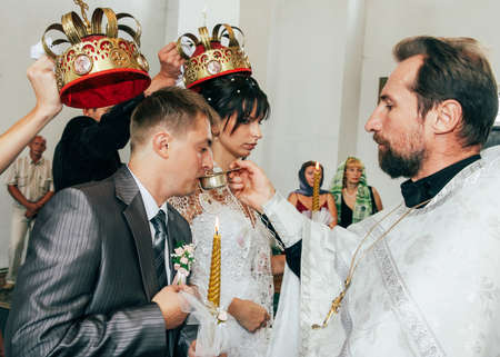 Lutsk, Volyn  Ukraine - August 30 2009: Couple taking communion during wedding ceremony in christian church