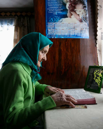 Beregnycia, Rivne  Ukraine - February 05 2010: Older women sitting in a room at the table and reads the Bible Editorial