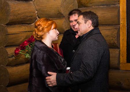 Lutsk, Volyn / Ukraine - November 17 2017: Woman with husband congratulates friend on his birthday at autumn night near restaurant