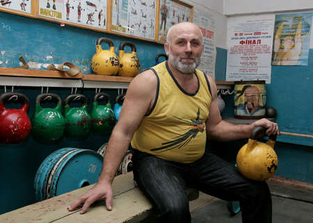 Novograd, Volyn  Ukraine - March 31 2009: Senior man posing with kettlebell in rural gym