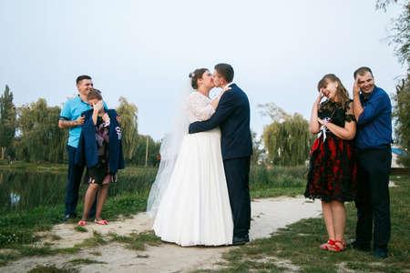 Lutsk, Volyn  Ukraine - September 16 2018: Funny portrait of newlywed couple kissing, bridesmaids and groomsmen hide eyes in park