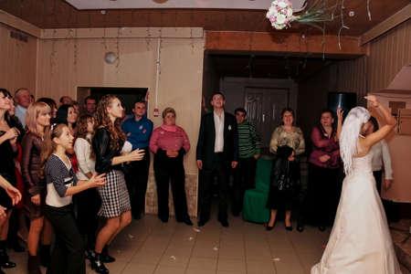 Lutsk, Volyn  Ukraine - October 12 2008: Happy bride throwing bouquet and having fun at the wedding reception in restaurant
