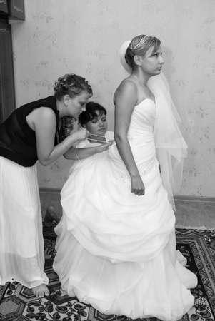 LUTSK, Volyn  UKRAINE - August 05 2012: Bridesmaids is helping the bride to dress