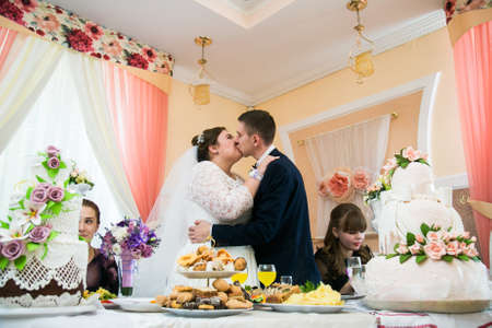 Lutsk, Volyn  Ukraine - September 16 2018: Bride and groom kissing between wedding cakes at wedding reception in restaurant Sajtókép