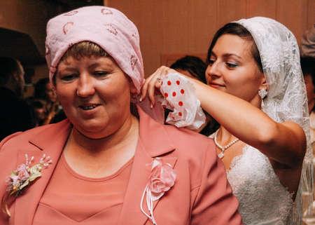 Lutsk, Volyn  Ukraine - October 14 2008: Bride wear a kerchief to mother-in-law after wedding ceremony at restaurant