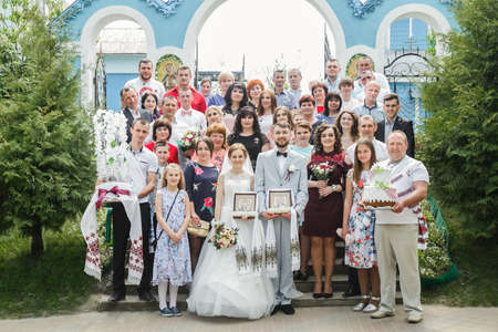 Cuman, Volyn  Ukraine - April 29 2018: Groom and bride with guests posing near church