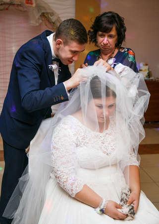 Lutsk, Volyn  Ukraine - September 16 2018: Mother and groom take off bride veil after wedding Sajtókép