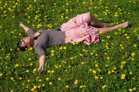 Frau liegt auf dem Feld im grünen Gras und Löwenzahn mit ausgestreckten Armen