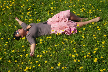 Woman lying on the field in green grass and dandelions with outstretched arms